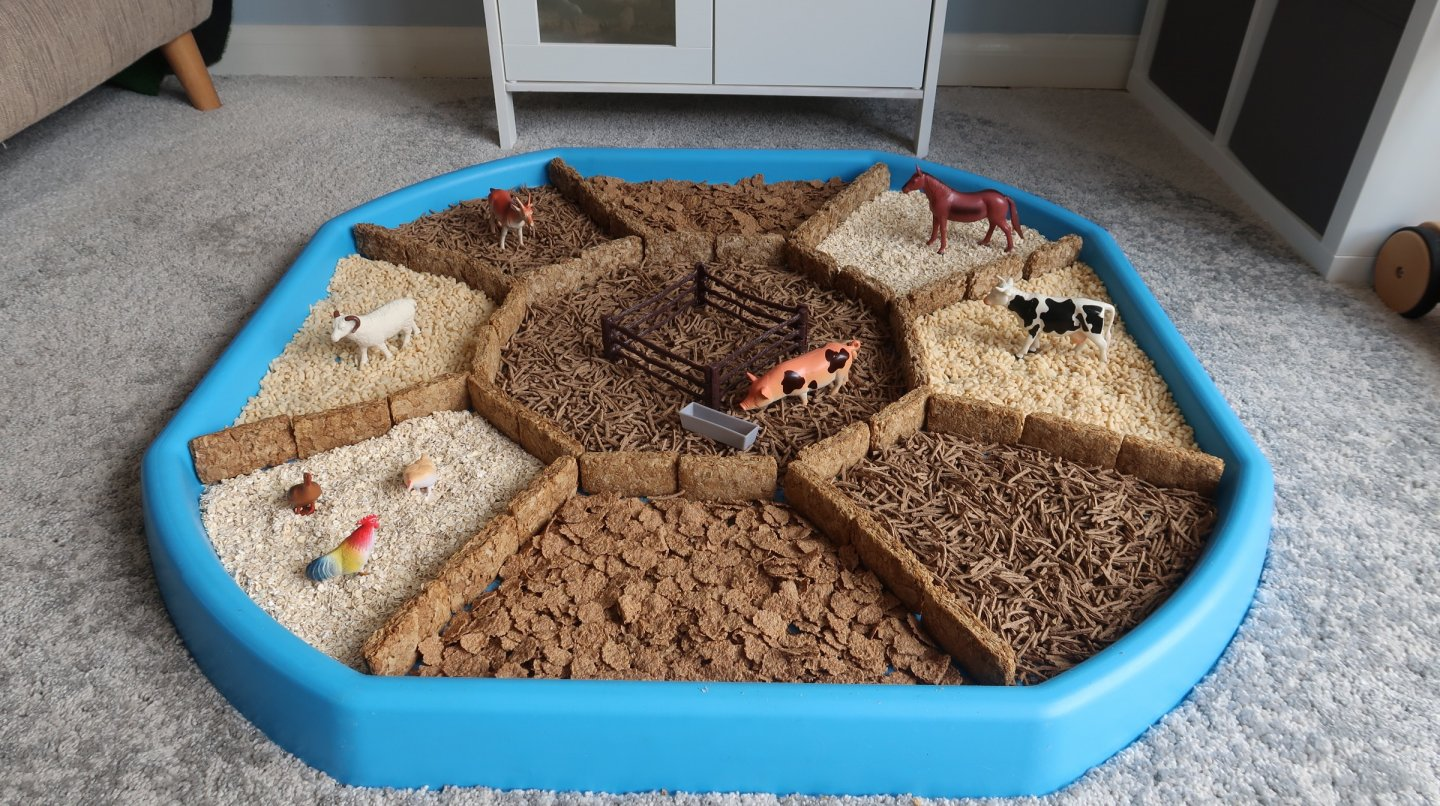 Farmyard sensory tuff spot EYFS activity. A tuff spot with different zones, divided by weetabix walls, with different cereals (rice puffs, all bran, porridge oats and bran flakes) in each zone.