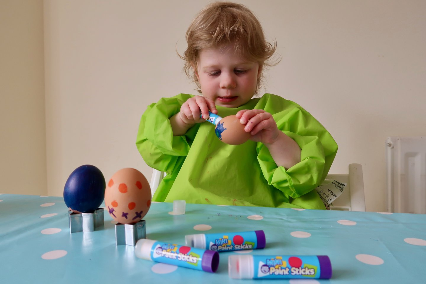 Using paint sticks to decorate boiled eggs for Easter.