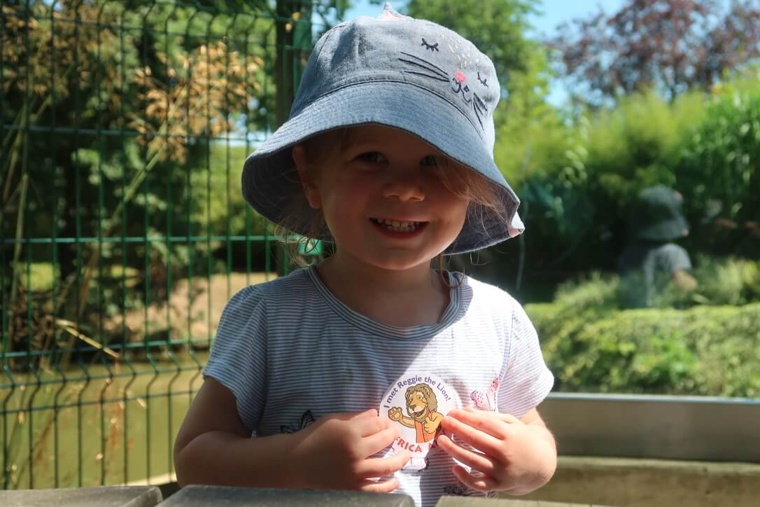 M smiles at the camera, touching her 'I met Reggie the lion at Africa Alive' sticker with pride.