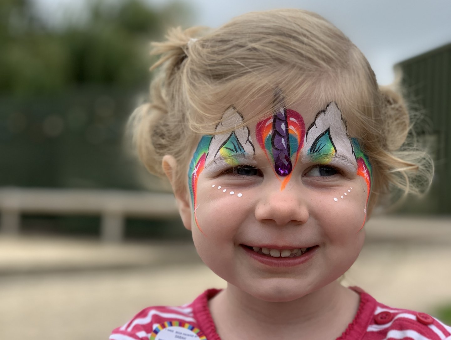 M has her face painted, with rainbows across her forehead and a purple unicorn horn, complete with purple 'jewel', in the centre.