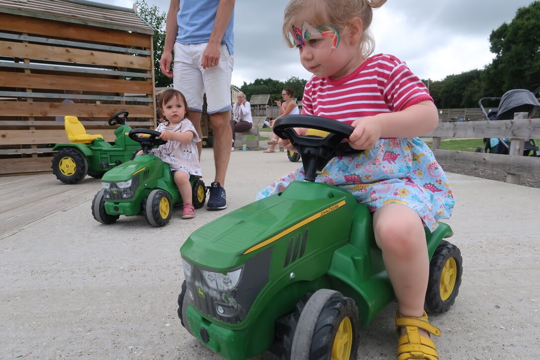 M and B sit on ride-on tractors.