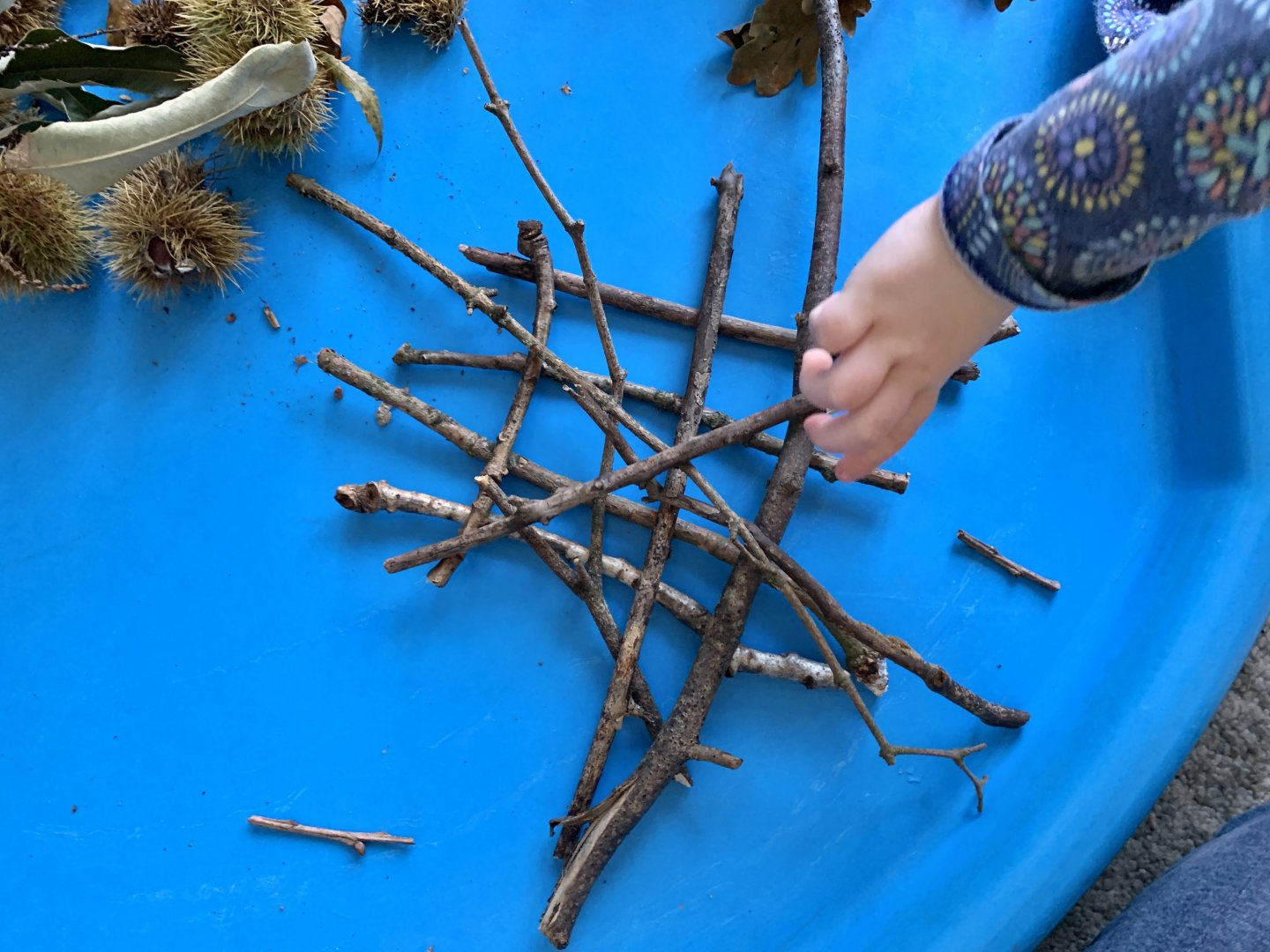 M places a twig on top of a crisscrossed pile of twigs.