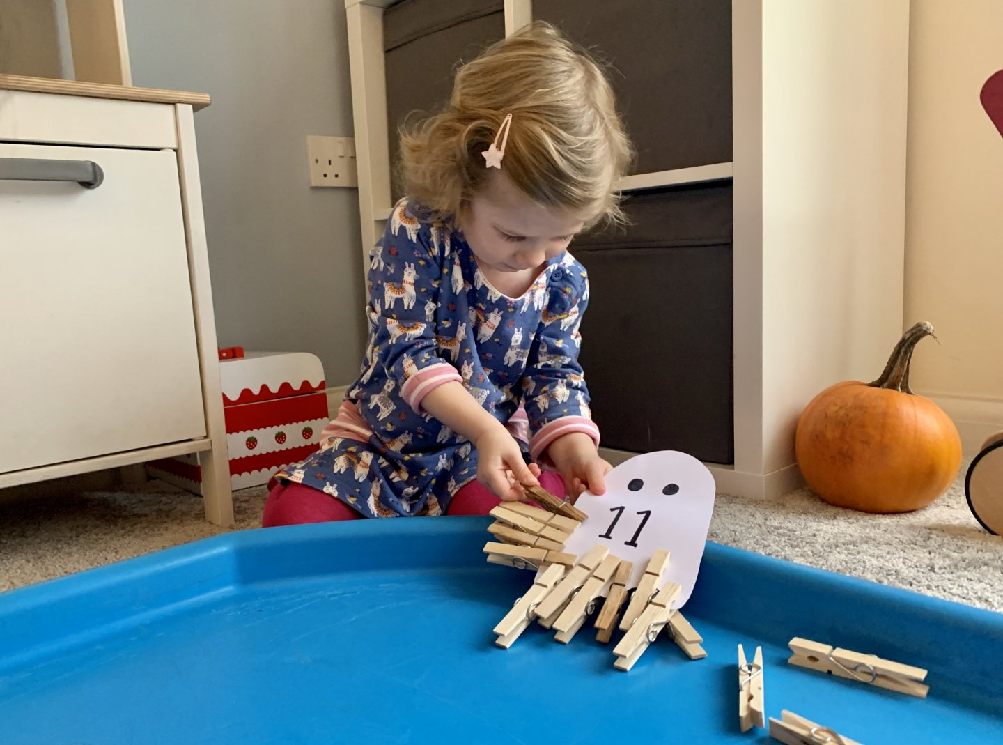 M clips a peg onto a ghost with the number 11 written on it. There are already 10 pegs on the ghost.