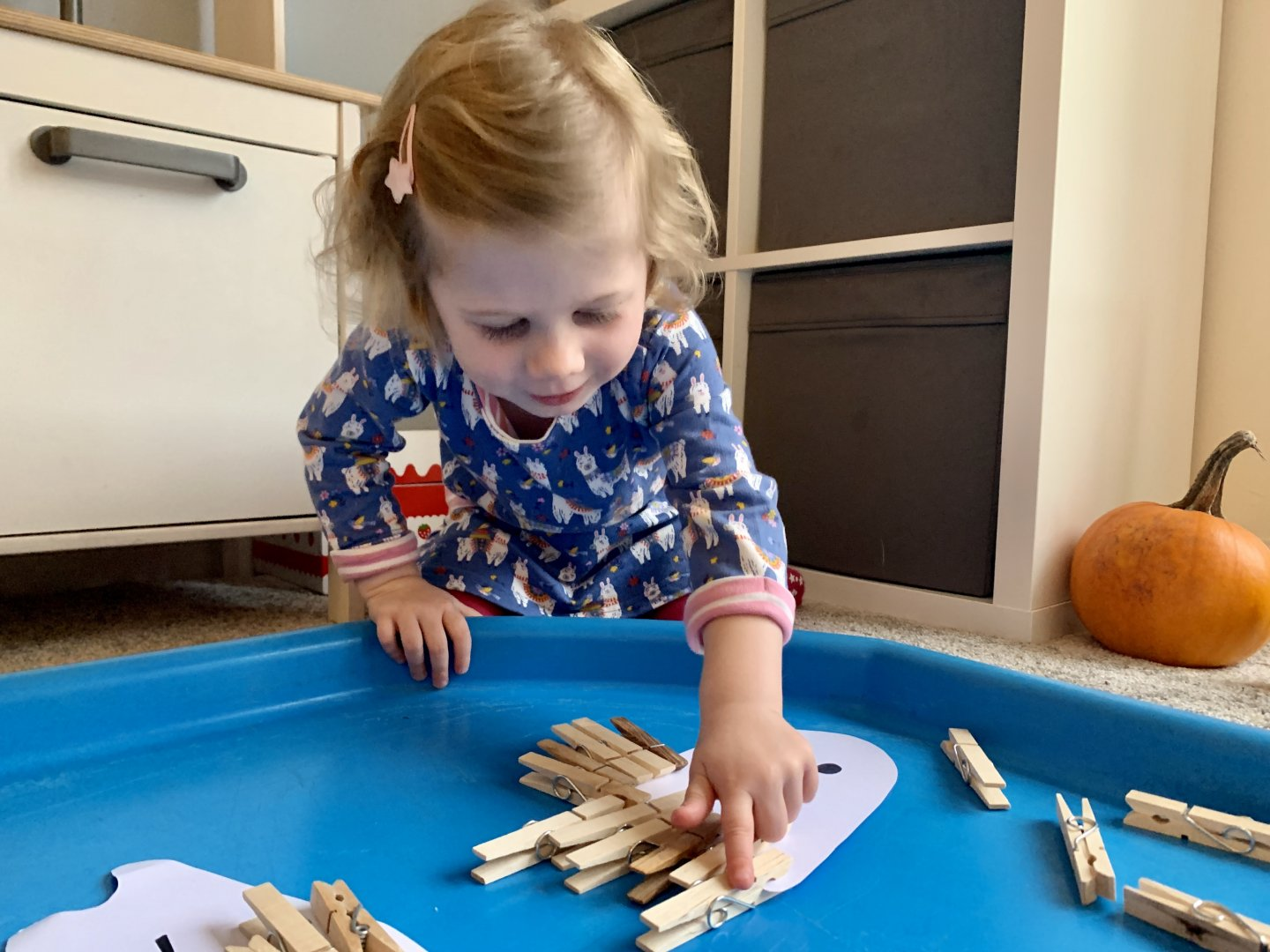 M uses her index finger to point at a peg as she counts the pegs on her cardboard ghost.