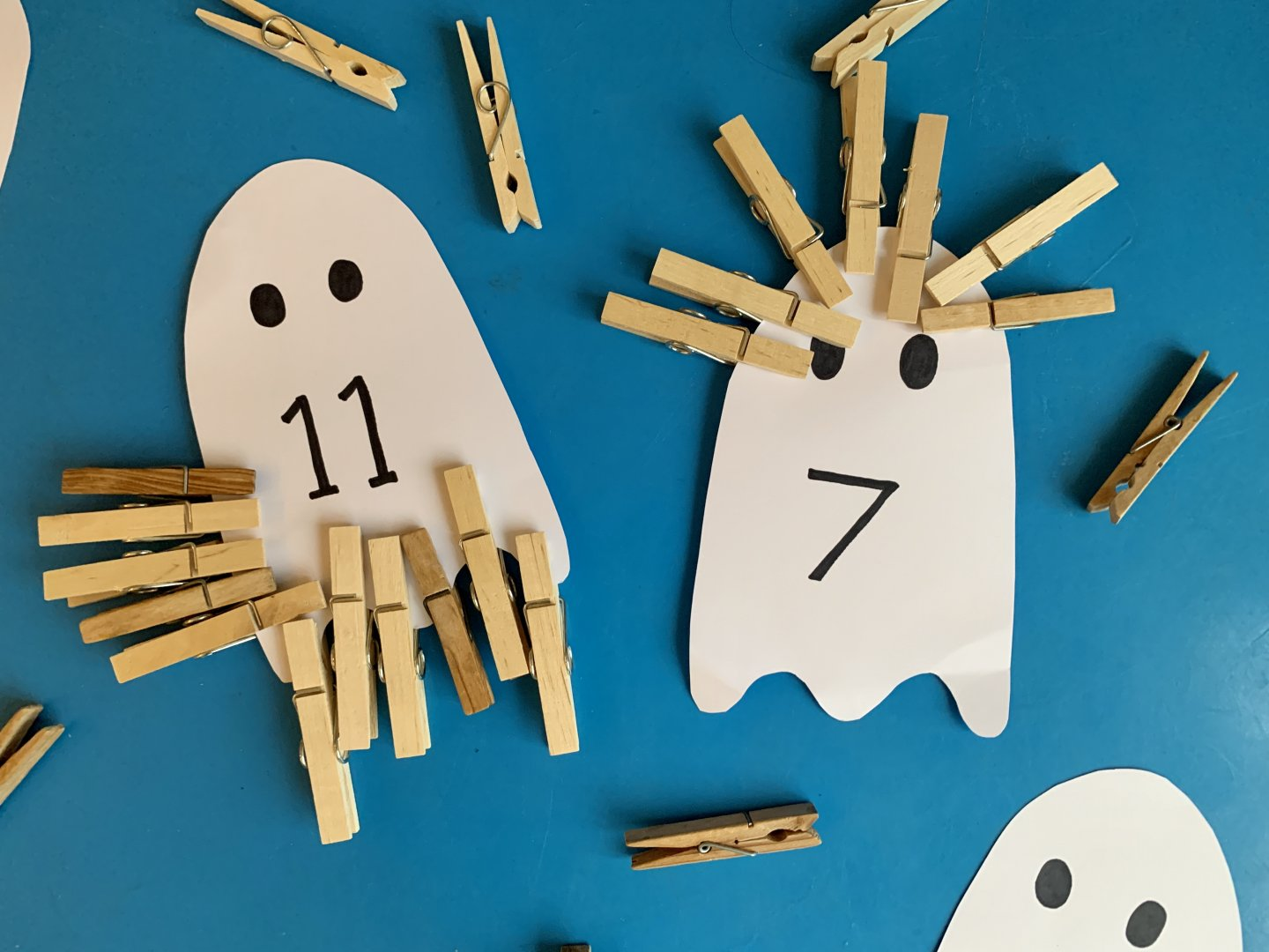 Two white card ghosts, one with a number 11 written on it and the other with number 7 written on it in black ink. Each ghost has the corresponding number of pegs clipped to it.
