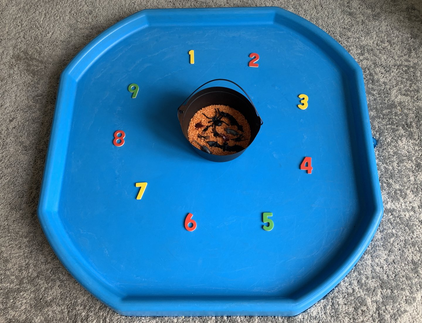 A wide shot of a blue tuff spot with a black plastic cauldron in the centre, filled with orange split lentils and plastic creepy crawlies, and surrounded by the numbers 1-9 arranged in a circle, in numerical order.