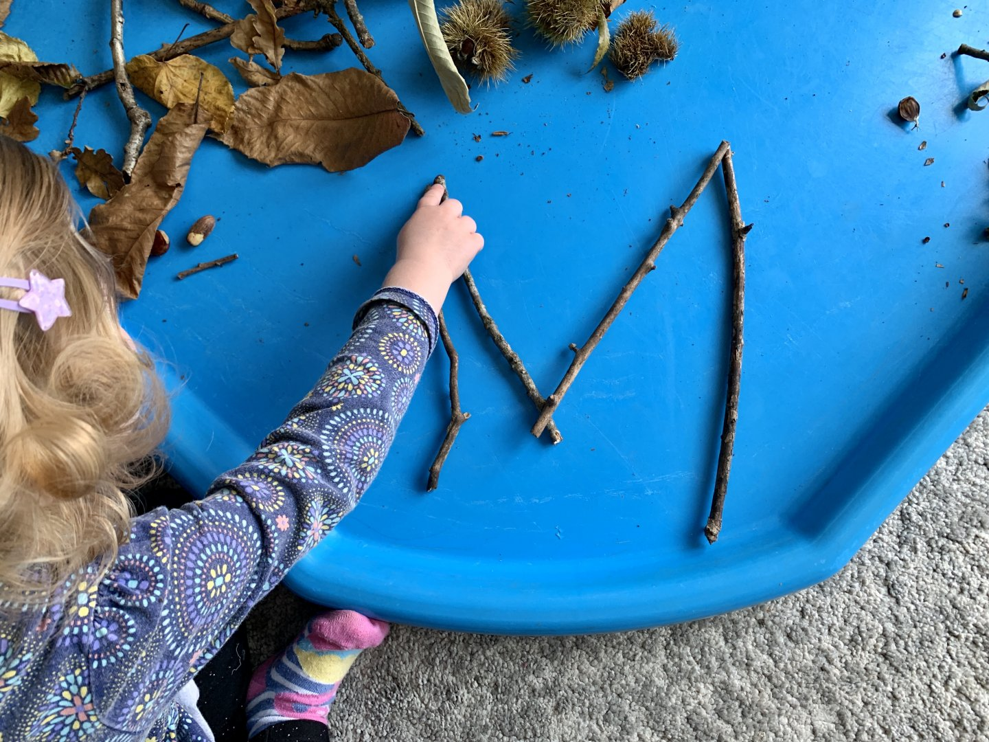 M uses her finger to trace the shape of the letter M, made out of twigs.