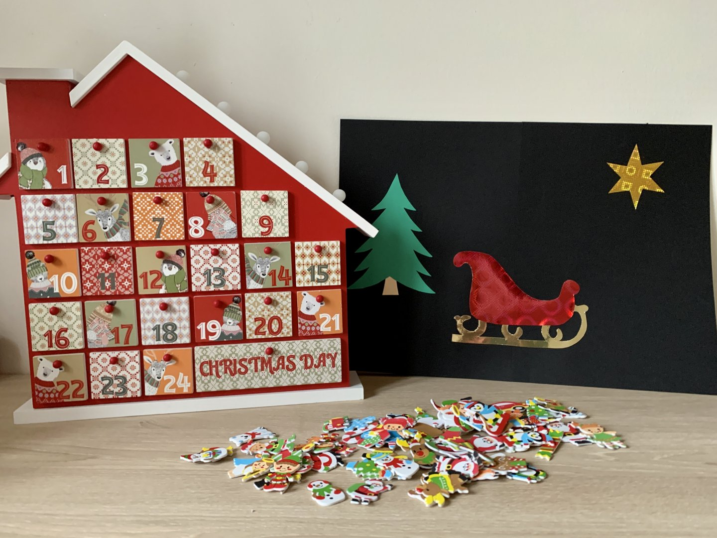 A wooden advent house stands next to a homemade A3 picture made with a black card background, sparkly red sleigh, gold star and green Christmas tree. A pile of Christmas-themed stickers are spread out on the desk in the foreground.