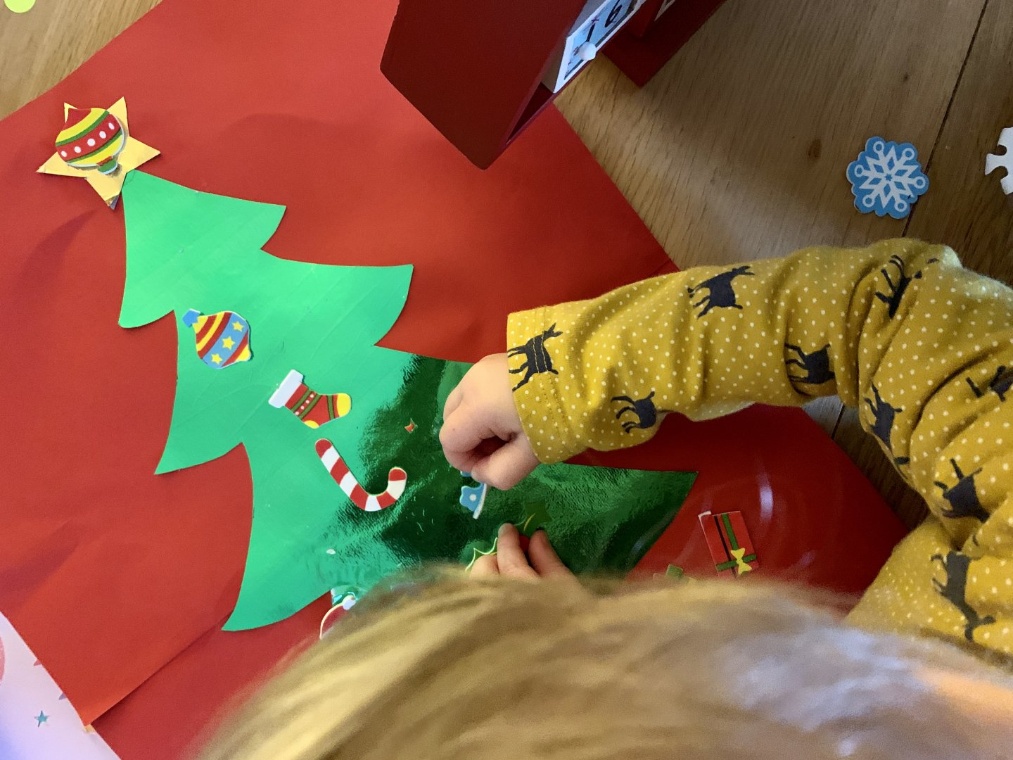 A toddler sticks foam Christmas stickers onto a picture of a shiny green Christmas tree.