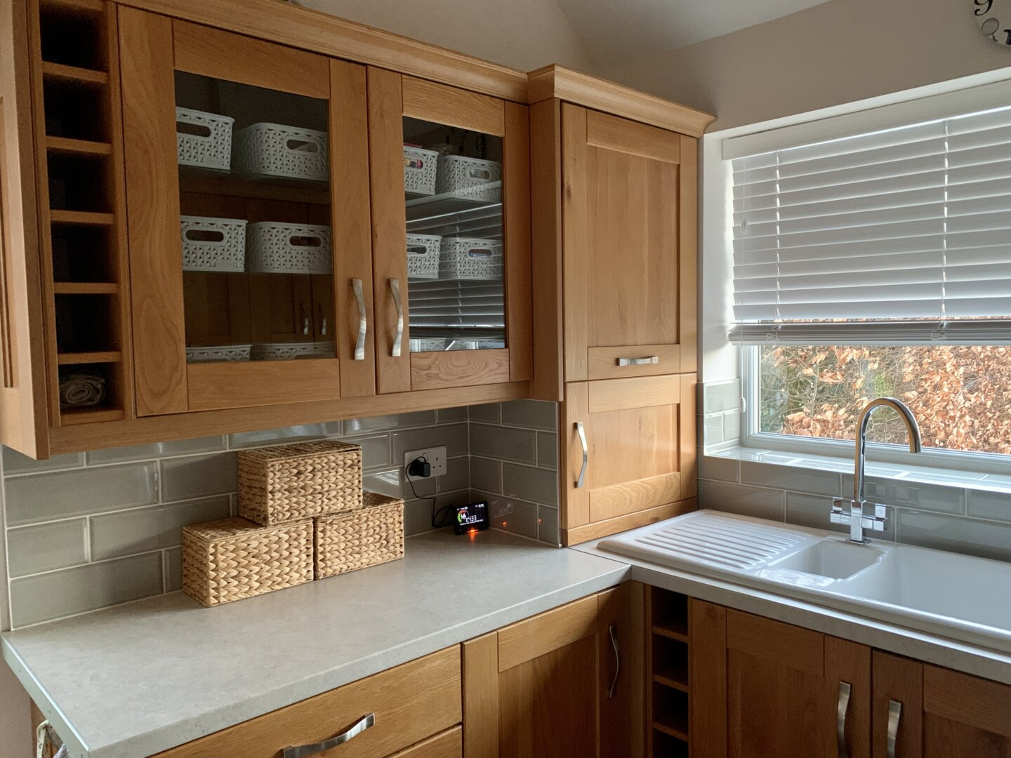 A freshly organised utility room with a double glass-fronted wall cupboard, with 12 small grey baskets inside. Three empty wicker baskets sit on a a plain grey worktop underneath, in front of sage green metro tiles. To the right is a ceramic double sink with a window above it.